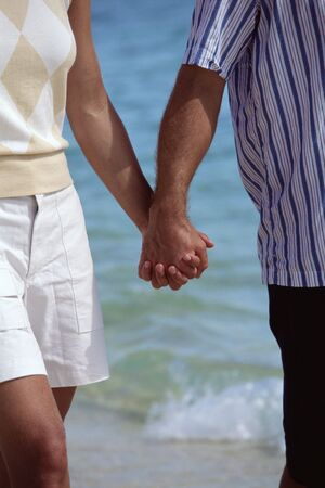 Couple holding hands outdoors at the beach (selective focus) photo
