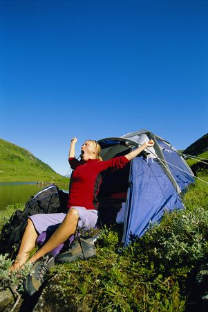 campsite: Woman outdoors at campsite by lake yawning and stretching
