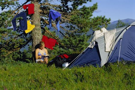 Woman outdoors at campsite reading book by hanging clothes photo