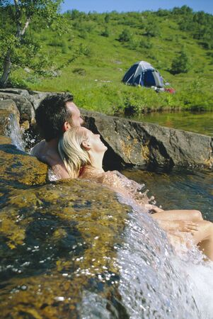 Couple outdoors by campsite relaxing in stream photo