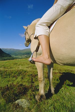 Woman outdoors riding horse in scenic location photo