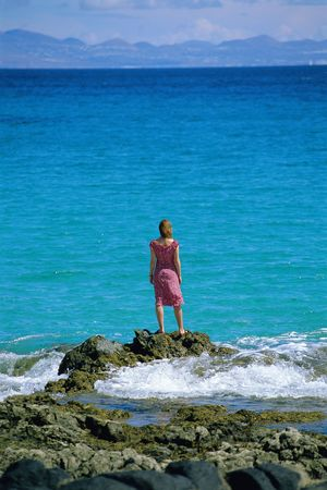 Woman outdoors standing on large rocks by the ocean photo