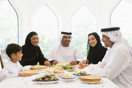 thobes: Family sitting at dinner table smiling (high key) Stock Photo