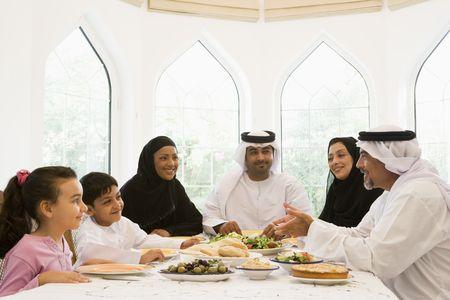 dishdasha: Family sitting at dinner table smiling (high key) Stock Photo