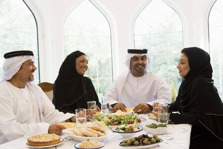 khameez: Two couples sitting at dinner table smiling (high key) Stock Photo