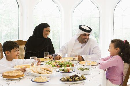 femmes muslim: Famille, assis � table souriant (haute cl�)  Banque d'images