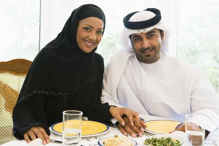 kanduras: Couple sitting at dinner table smiling (high key)