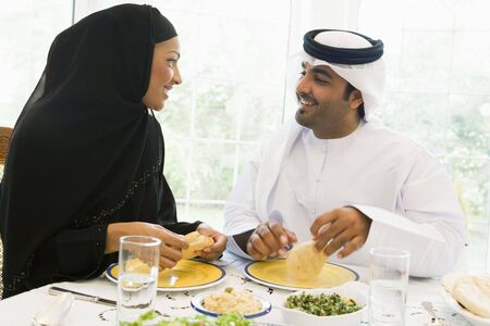 thobes: Couple sitting at dinner table smiling (high key)