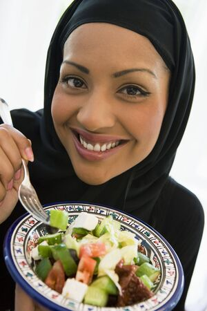 cutouts: Woman holding bowl of salad and smiling (studio shotselective focus)