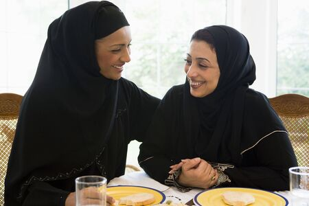 jilaabah: Two women sitting at dinner table smiling (high key) Stock Photo