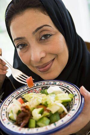 jilbab: Woman holding bowl of salad and smiling (high keyselective focus)