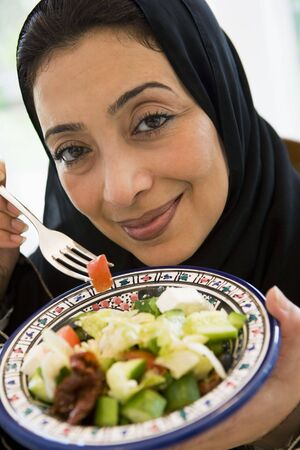 jilaabah: Woman holding bowl of salad and smiling (high keyselective focus)