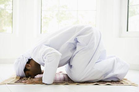 Man indoors praying on mat (high key) photo