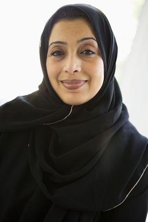 jilaabah: Woman standing indoors smiling (high key)