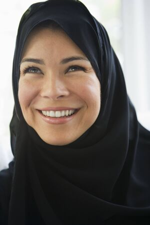 jilaabah: Woman standing indoors smiling (high key)