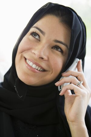 parlours: Woman indoors on cellular phone smiling (high key) Stock Photo