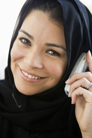 jilaabah: Woman indoors on cellular phone smiling (high key) Stock Photo