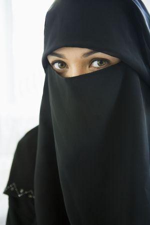 Woman wearing black veil indoors (high key)