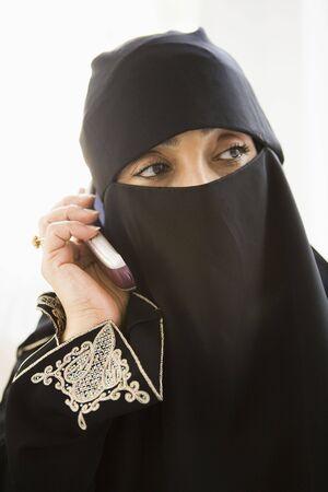 jilaabah: Woman indoors on cellular phone wearing veil (high key)