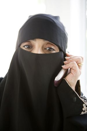 parlours: Woman indoors on cellular phone wearing veil (high key)