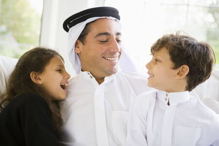 Father and two young children sitting in living room smiling (high key/selective focus) Stock Photo - 3186168