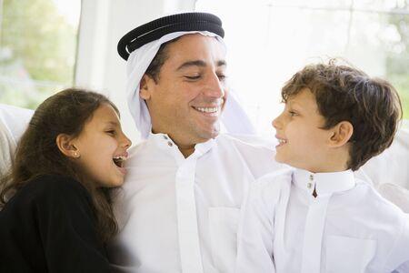 thobes: Padre y dos ni�os peque�os sentados en sal�n sonriente (clave de alta  selectiva enfoque)