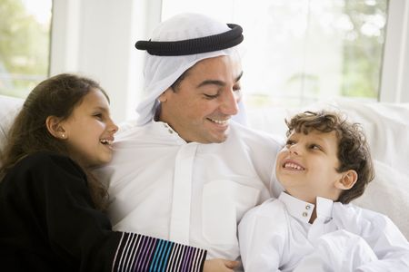 agal: Father and two young children sitting in living room smiling (high keyselective focus) Stock Photo