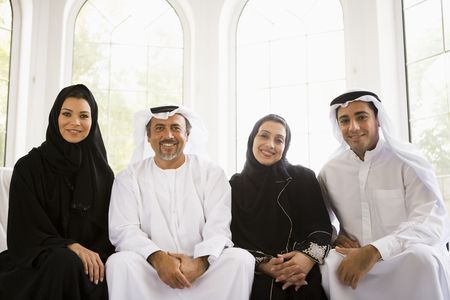 thobes: Two couples sitting in living room smiling (high keyselective focus)