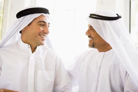 high key: Due uomini seduti al chiuso di parlare e sorridente (alta chiave)
