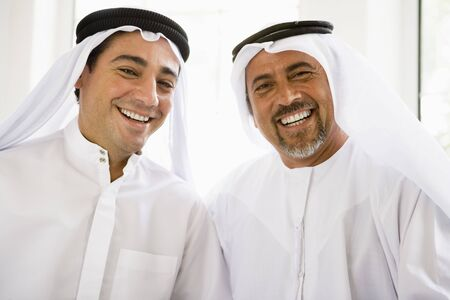 kanduras: Two men sitting indoors smiling (high key)