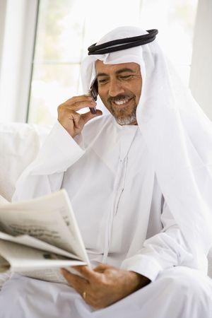 thawbs: Hombre sentado adentro con peri�dico y sonriente tel�fono celular (clave de alta  selectiva enfoque)
