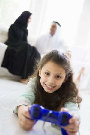 Daughter in living room playing video games smiling with parents in background (high keyselective focus) photo