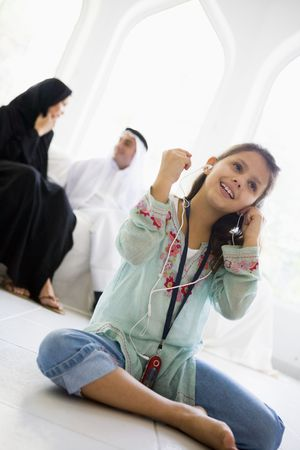 middle easterners: Daughter in living room listening to MP3 player and smiling with parents in background (high keyselective focus)