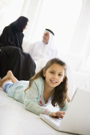 Daughter in living room using laptop and smiling with parents in background (high keyselective focus) photo