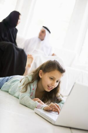 lying on side: Young girl in living room using laptop and smiling with parents in background (high keyselective focus)