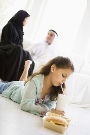Young girl with fast food in living room with parents in background (high keyselective focus) photo