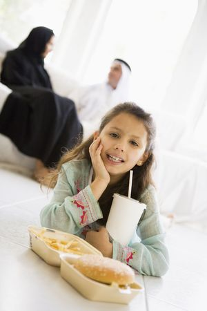 Young girl with fast food in living room smiling with parents in background (high keyselective focus) photo