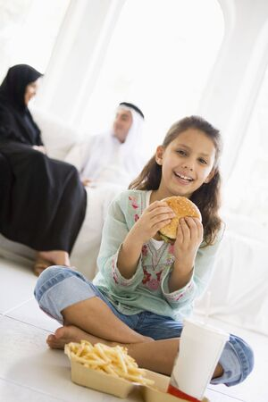 Young girl with fast food in living room smiling with parents in background (high key/selective focus) Stock Photo - 3194539