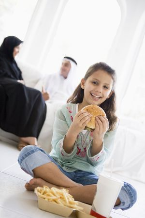 middle easterners: Young girl with fast food in living room smiling with parents in background (high keyselective focus)
