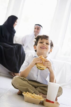 Young boy with fast food in living room laughing with parents in background (high key/selective focus)