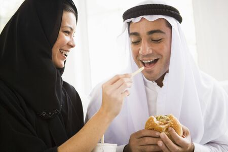 Couple eating fast food in living room and smiling (high key/selective focus) Stock Photo - 3187002