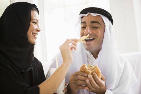 khameez: Couple eating fast food in living room and smiling (high keyselective focus)