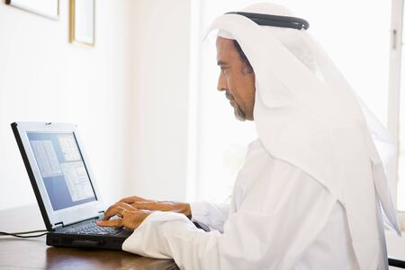 thobes: Man in office with laptop (high keyselective focus)
