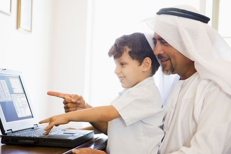 dishdashas: Man and young boy in office with laptop pointing and smiling (high keyselective focus) Stock Photo