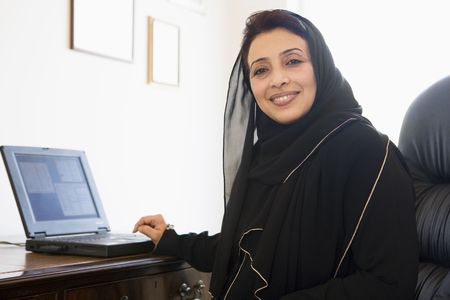 house robes: Woman in office with laptop smiling (high keyselective focus)