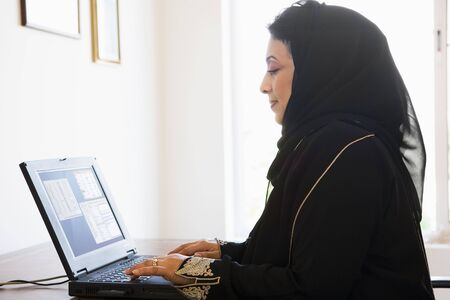 jilaabah: Woman in office with laptop (high keyselective focus)