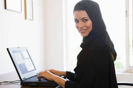 jilaabah: Woman in office with laptop smiling (high keyselective focus)