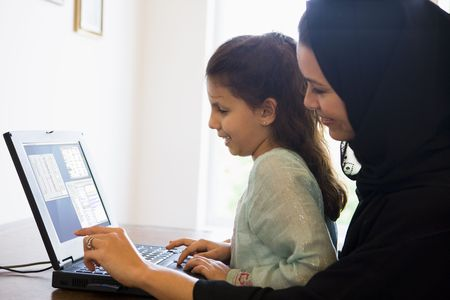 windowpanes: Mother and daughter in office with laptop smiling (high keyselective focus)