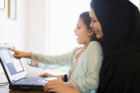 windowpanes: Mother and daughter in office with laptop pointing and smiling (high keyselective focus)