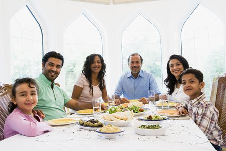 Family sitting at dinner table smiling (high key) Stock Photo - 3186929